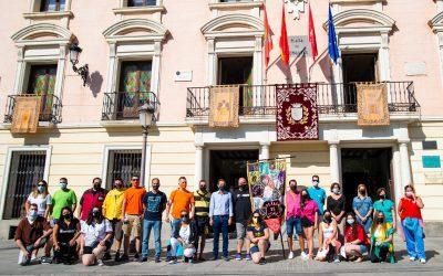 La corporación municipal y las peñas festivas que participan en el Verano en Fiestas 2021 de Alcalá colocan su estandarte en el balcón del Ayuntamiento